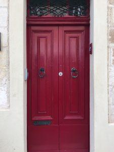 Burgundy red door with wrought iron double door knockers